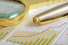 Positive Earning. A pen and a magnifying glass focusing on a chart Royalty Free Stock Photo