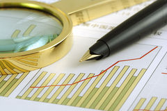 Positive Earning. A pen and a magnifying glass focusing on a chart Stock Photos