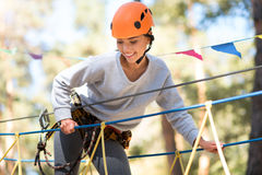 Positive elated woman looking down. How interesting. Pleasant glad good looking woman looking down and smiling while enjoying her high wire activities Stock Photos