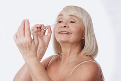 Positive elated woman using a cotton bud. Daily skin care. Pleasant elated grey haired woman holding a cotton bud and looking at her hand while putting on cream Royalty Free Stock Photography