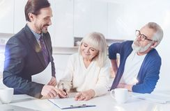 Positive elderly couple meeting with their insurance agent. Just here. Cheerful elderly couple sitting in the kitchen and signing contract while meeting with the Royalty Free Stock Photo