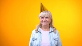 Positive elderly lady in party hat smiling to camera, birthday celebration. Stock photo stock images