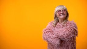 Positive elderly lady in pink coat and round sunglasses crossing hands on chest stock photo