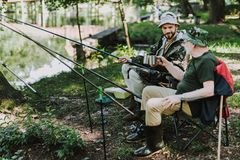 Cheerful father and son fishing together on the river bank royalty free stock photo