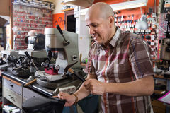 Positive Elderly specialist stitching shoes on leather sewing ma Royalty Free Stock Image