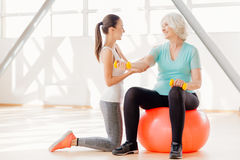 Positive elderly woman exercising with dumbbells. Fitness workout. Positive joyful elderly women holding dumbbells and exercising with them while sitting on the stock photography