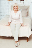 Positive elderly woman siting on the bed royalty free stock photography