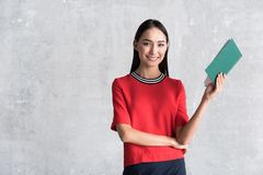 Positive elegant young woman is enjoying her hobby. Sharing gladness. Portrait of happy stylish businesswoman is standing with book and looking at camera with royalty free stock photography