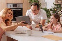 Positive Eltern, die mit Kind zu Hause malen genießen Stockbilder