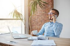 Positive emotions. Business concept. Cheerful professional adult caucasian finance manager in glasses and blue shirt. Sitting in company office, laughing during stock image