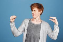 Positive emotions. Funny young attractive ginger guy in gray t-shirt under cardigan talking to his hands, making silly Stock Photos
