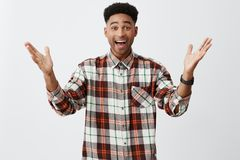 Positive emotions. Isolated portrait of young happy tan-skinned guy with afro haircut in long-sleeved checkered shirt Royalty Free Stock Image