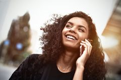 Positive emotions. Lifestyle concept. Close up of young mixed race woman use a phone royalty free stock photo