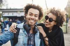 Positive and emotive young african-american people cuddling or hugging while walking in park, joking and being in good. Mood, wearing trendy outfit. Friendship stock image
