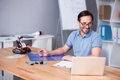 Positive engineer sitting at the table. Involved in project. Cheerful professional engineer working on the project and sitting at the table while expressing stock photo