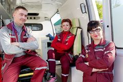Positive ER Doctor with Paramedics Colleagues in Ambulance Car Stock Photo