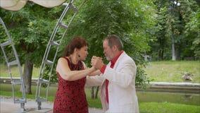 Positive erwachsene Freunde, die Paartanz im Garten tanzen tanzender Tango der älteren Paare Älteres Mann- und Frauentanzen lizenzfreie stockbilder
