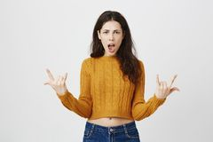 Positive and excited european girl wearing trendy cropped sweater, showing rock signs and screaming at camera standing. Over gray background. Woman thinks Stock Photo
