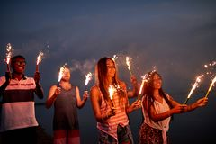 Cheerful friends with sparklers on summer beach stock images
