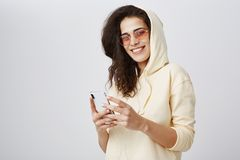 Positive expressive girl with curly hair wearing yellow hoodie and trendy sunglasses smiling broadly at camera while. Holding new smartphone and listening music royalty free stock image
