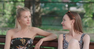 Two young girls sitting on bench in a park enjoying summer and chatting. Positive face expressions, emotions, feelings, body language. Portrait of two happy stock video