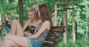 Two young girls sitting on bench in a park enjoying summer and chatting. Positive face expressions, emotions, feelings, body language. Portrait of two happy stock video footage