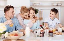 Positive family enjoying breakfast together Stock Images