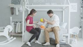 Happy parents playing with infant girl in bedroom stock video footage