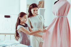 Positive family looking at new dress of their own creation royalty free stock photography