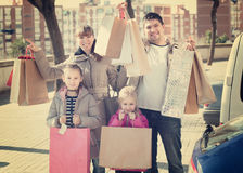 Positive family portrait with purchases in bags Royalty Free Stock Photos