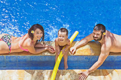 Positive family relax in the outdoor tropical pool Royalty Free Stock Photos