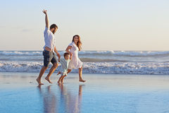 Positive family running along sea edge on the beach Royalty Free Stock Photo