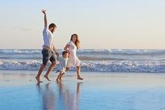 Positive family running along sea edge on the beach royalty free stock photo