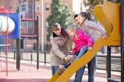 Positive family spending time at children slide royalty free stock image