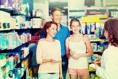 Positive family of three consulting druggist. Positive family of three persons consulting druggist in pharmacy. Focus on mature woman Stock Photos