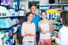 Positive family of three consulting druggist. Positive family of three persons consulting druggist in pharmacy. Focus on mature woman Royalty Free Stock Photo