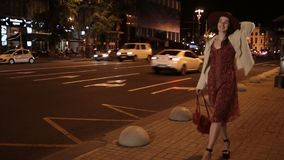 Positive fashionable woman walking on night street stock video