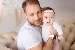 Positive father expressing love to his kid at home. Full of positivity. Happy smiling young father sitting on the couch at home and hugging his child while Royalty Free Stock Images