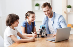 Positive father playing with kids. Modern device. Cheerful content positive smiling father and his children sitting at the table and using laptop while stock photography