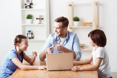 Positive father sitting at the table with kids stock photography