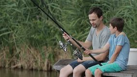 Positive father and son fishing together on pond stock footage