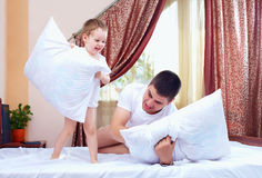 Positive father and son having fun at home, pillow fight. Cute positive father and son having fun at home, pillow fight stock image