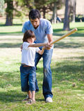 Positive father teaching baseball to his son. In the park duing a sunny day Royalty Free Stock Images