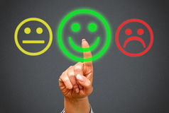 Positive feedback. Finger of person pressing positive feedback smiling face on interactive display screen