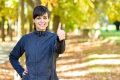 Positive female athlete with thumbs up. Charming sportswoman with thumbs up friendly. Beautiful female athlete in positive attitude Royalty Free Stock Images