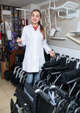 Positive female consultant selling wheelchairs in special store. With orthopaedic equipment Stock Photo