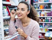 Positive female customer buying mascara Stock Photography