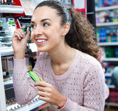 Positive female customer buying mascara. In makeup section Stock Image