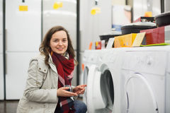 Positive female customer looking at dryers Stock Image