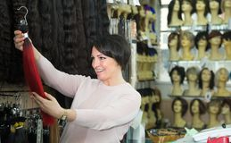 Positive female customer selecting clip-in hair extension at sho Stock Image